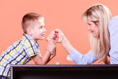 Mother and son arm wrestle sit at table. Stock Image