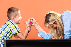 Mother and son arm wrestling. Stock Image