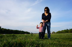 Mother and son. Mother assisting baby boy with walking on green grass Royalty Free Stock Photo
