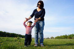 Mother and son. Mother assisting baby boy with walking on green grass Stock Image
