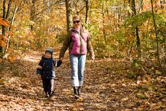 Mother and son in autumn forest stock images