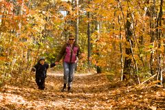 Mother and son in autumn forest Stock Photo