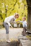 Mother and son in the autumn forest Stock Photos