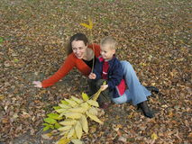 Mother with son with autumn leaves. Mother with son with and on autumn leaves royalty free stock photo