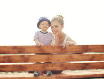 Mother and son baby sitting together on the bench Stock Photography