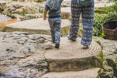 Mother and son in the background of beautiful cascading Datanla waterfall In the mountain town Dalat, Vietnam.  Stock Photo