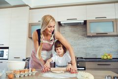 Mother and son bake cakes in the kitchen.  stock photography