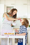 Mother and son baking cake in kitchen. Mother and son baking fruit cake together in kitchen with red currants stock photography