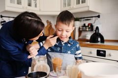 Mother and son baking cake in the kitchen. Lifestyle casual capture of family cooking. In real life interior royalty free stock photography