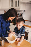 Mother and son baking cake in the kitchen. Lifestyle casual capture of family cooking. In real life interior stock photography