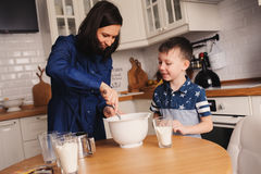 Mother and son baking cake in the kitchen. Lifestyle casual capture of family cooking. In real life interior Stock Photos