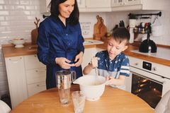 Mother and son baking cake in the kitchen. Lifestyle casual capture of family cooking. In real life interior royalty free stock photo