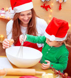 Mother with son baking Christmas cookies. At home, with pleasure cooking together, wearing red Santa hats, preparing tasty festive dinner Stock Photos