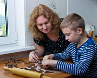 Mother and son baking cookies. Mother and son making gingerbread cookies royalty free stock photo