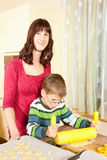 Mother and son are baking. Family baking Christmas cookies in the kitchen Stock Photos
