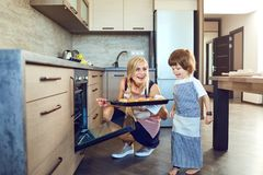 Mother and son with baking in the kitchen indoors.  royalty free stock photography