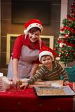 Mother and son baking together for christmas. Mother and son baking cake together for christmas, smiling royalty free stock image