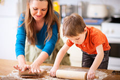 Mother and son baking. Young mother and her little son baking cookies together at home kitchen stock photos