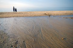 Mother and son on beach. Wide beach with water stream. Empty horizon, serene and calm mood. Two people (mother and son) in the distance Royalty Free Stock Photos