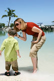 Mother and son on beach. Mother tending to her son on a beach Royalty Free Stock Photos