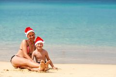 Mother and son on the beach on Christmas. Mother and son wearing santa hat having fun on the beach Stock Photos