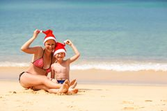 Mother and son on the beach on Christmas. Mother and son wearing santa hat having fun on the beach Royalty Free Stock Images