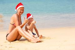 Mother and son the beach on Christmas. Mother and son wearing santa hat having fun on the beach Stock Image