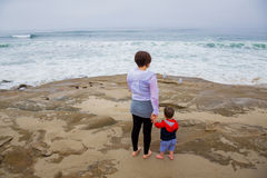 Mother and Son at Beach. Mother holding the hand of her son at the beach looking towards the waves, keeping her boy safe Royalty Free Stock Image