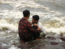 Mother and son on beach. Mother holding onto her son on a rocky beach with sea waves crashing in at Digha, West Bengal, India Royalty Free Stock Photo
