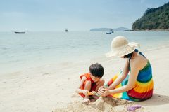 A mother and son on beach outdoors Sea and Blue sky stock images
