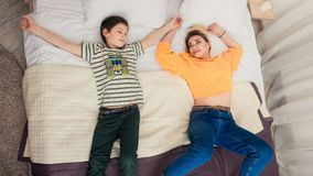Mother with son on bed, mother and son having fun. Happy mom and her teenager son lying on bed, mother with child relaxing, modern mom with kid at home Royalty Free Stock Photo