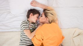 Mother with son on bed, mother and son having fun. Mother with son on bed, mother kissing her son, mother and son having fun, mom and her teenager son lying on Royalty Free Stock Image