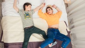 Mother with son on bed, mother and son having fun. Mom and her teenager son lying on bed, mother with child relaxing, modern mom with kid at home, top view Stock Photos