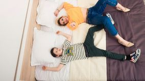 Mother with son on bed, mother and son having fun. Happy mom and her teenager son lying on bed, mother with child relaxing, modern mom with kid at home Royalty Free Stock Photos