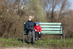 Mother with son on a bench Stock Images