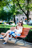 Mother and son on bench in park Stock Image