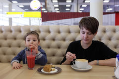 Mother and son with beverages. In the cafe Royalty Free Stock Image