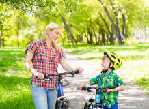 Mother and son on the bikes in the park Royalty Free Stock Photos