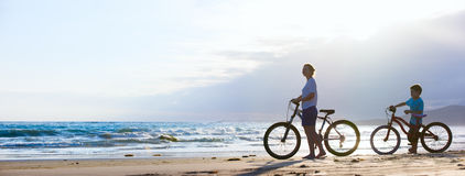Mother and son biking at beach Stock Photos