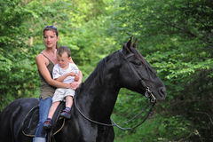 Mother, son and black horse Stock Image