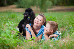 Mother with son and a black poodle Stock Photo