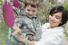 Mother and son in blooming garden decorating for Easter Stock Photos
