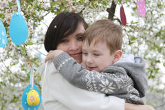 Mother and son in blooming garden decorating for Easter Stock Images