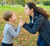 Mother and son blowing dandelion Royalty Free Stock Photos