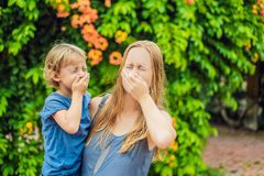 Mother and son blowing nose in front of blooming tree. Spring allergy concept. Children`s allergies royalty free stock image