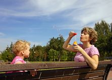 Mother and son blowing soap bubbles Stock Photography