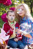 Mother and son blowing soap bubbles. Outdoors on sunny day Stock Images