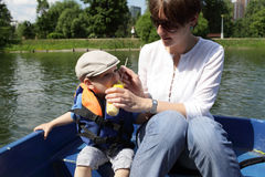 Mother with son in the boat. Mother with her son eating corn in the boat Stock Photo
