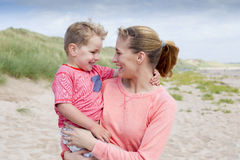 Mother and Son bonding. A Young mother with her son at the beach. They are looking at each other and smiling royalty free stock photography