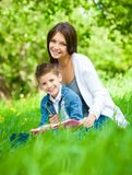 Mother and son with book in green park Royalty Free Stock Image